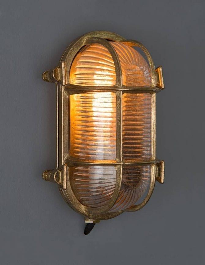 lit steve brass bulkhead outdoor lights against grey background