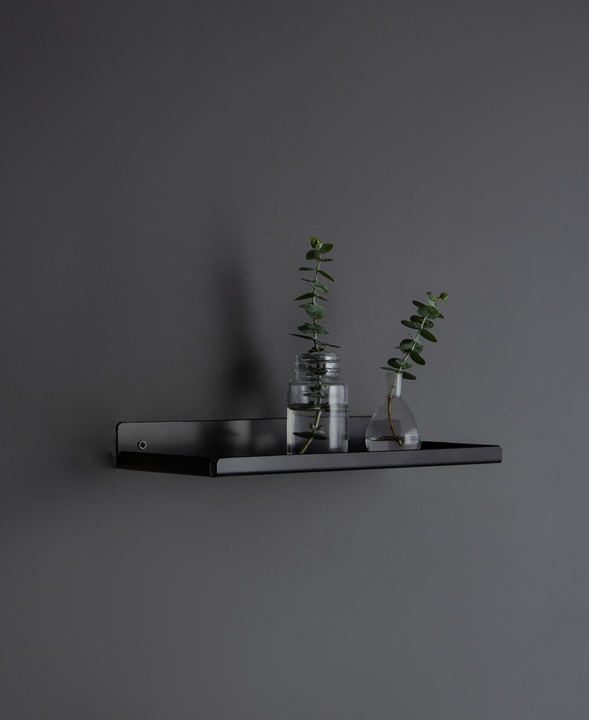 assam black metal wall shelf with glass vases on a dark grey wall