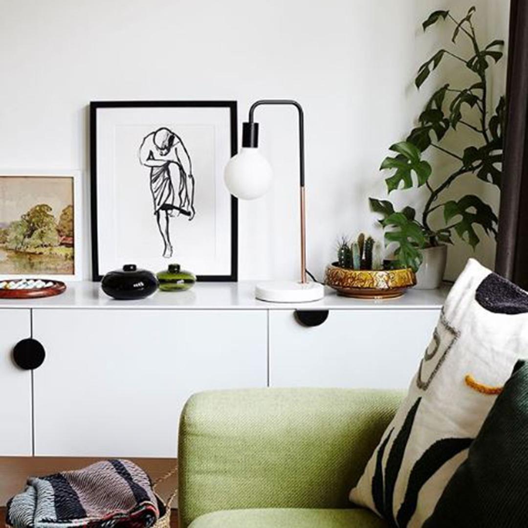 black mezzaluna pull handles on white unit in a white living room