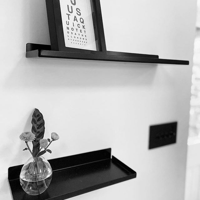 assam shelf holding a small vase of flowers and a pice of artwork