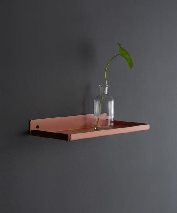 pink chai metal wall shelf with glass vase on a dark grey wall