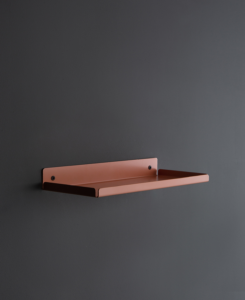 pink chai metal wall shelf on a dark grey wall