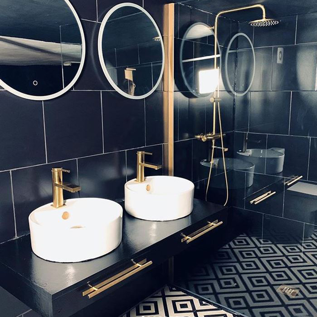 gold skyscraper handle with plate on black drawer in black, white and gold bathroom
