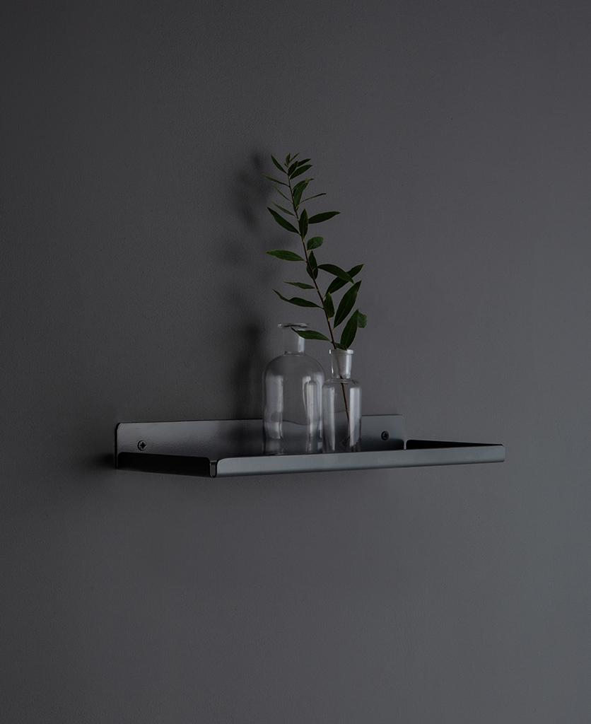 earl grey shelf with glass vases on a dark grey wall