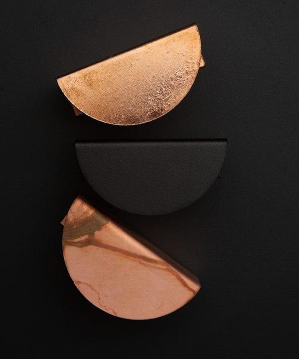 mezzaluna pull handle group of three handles in black, copper and tarnished copper against black background