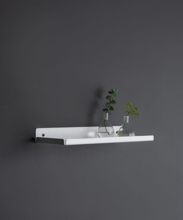 white wall shelf with glassware and vases on a dark grey wall