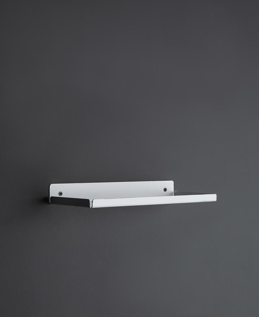 white metal wall shelf on a dark grey wall