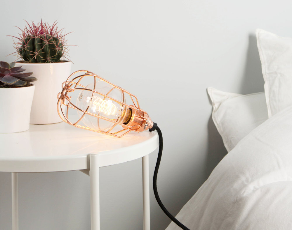 bedside table lamp featuring copper cage light shade, filament light bulb, copper bulb holder and black fabric lighting cable in a white bedroom