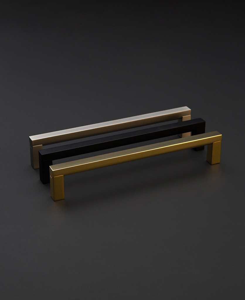 metal long door pull handles in black silver and gold against black background