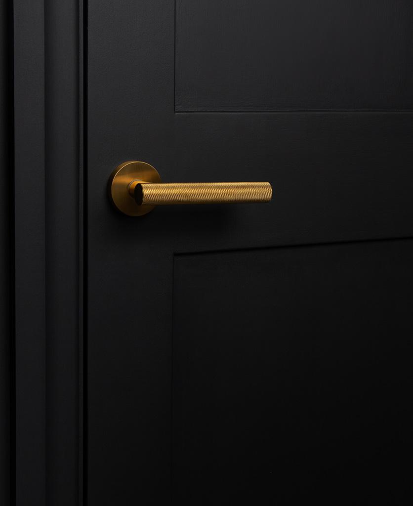 hirst gold modern door handle on black door
