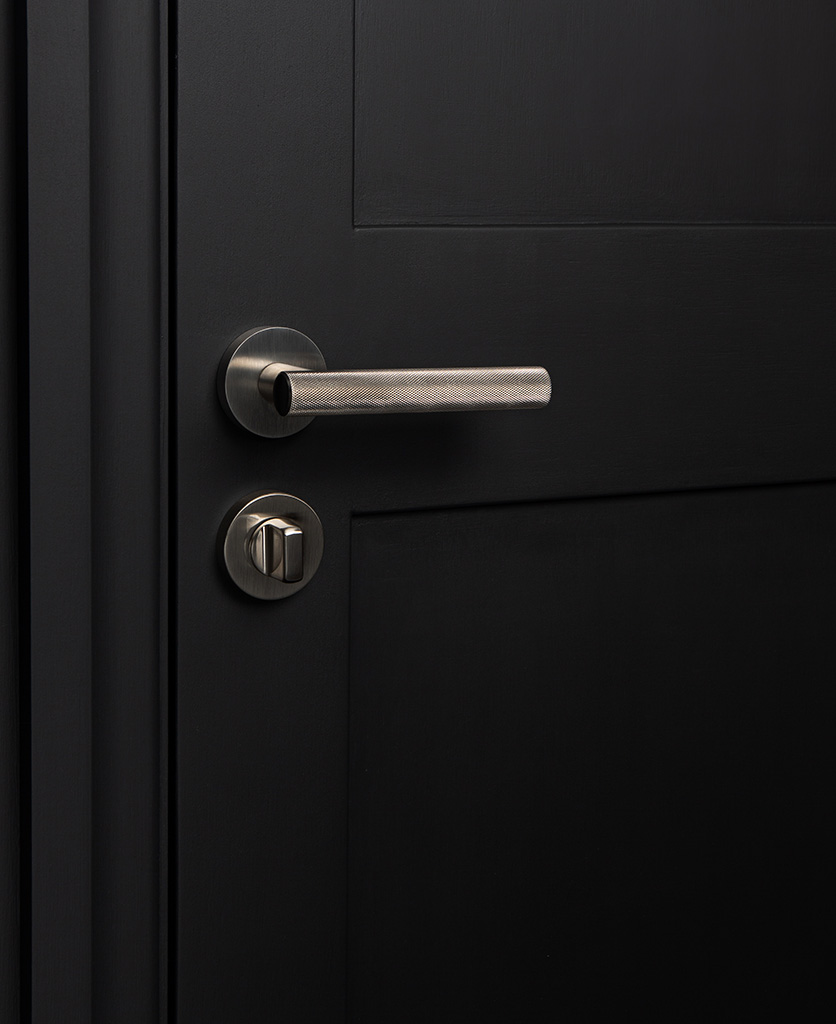 hirst silver modern door handle with thumb lock on black door