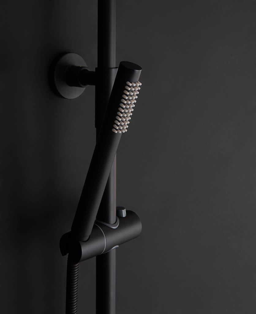 Close up of black tinago wall-mounted shower handheld shower bar on black background