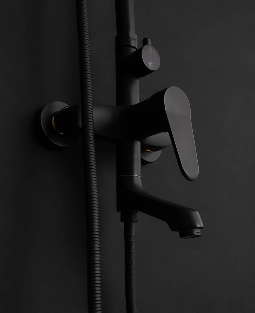 Close up of Tinago wall-mounted shower mixer on black background