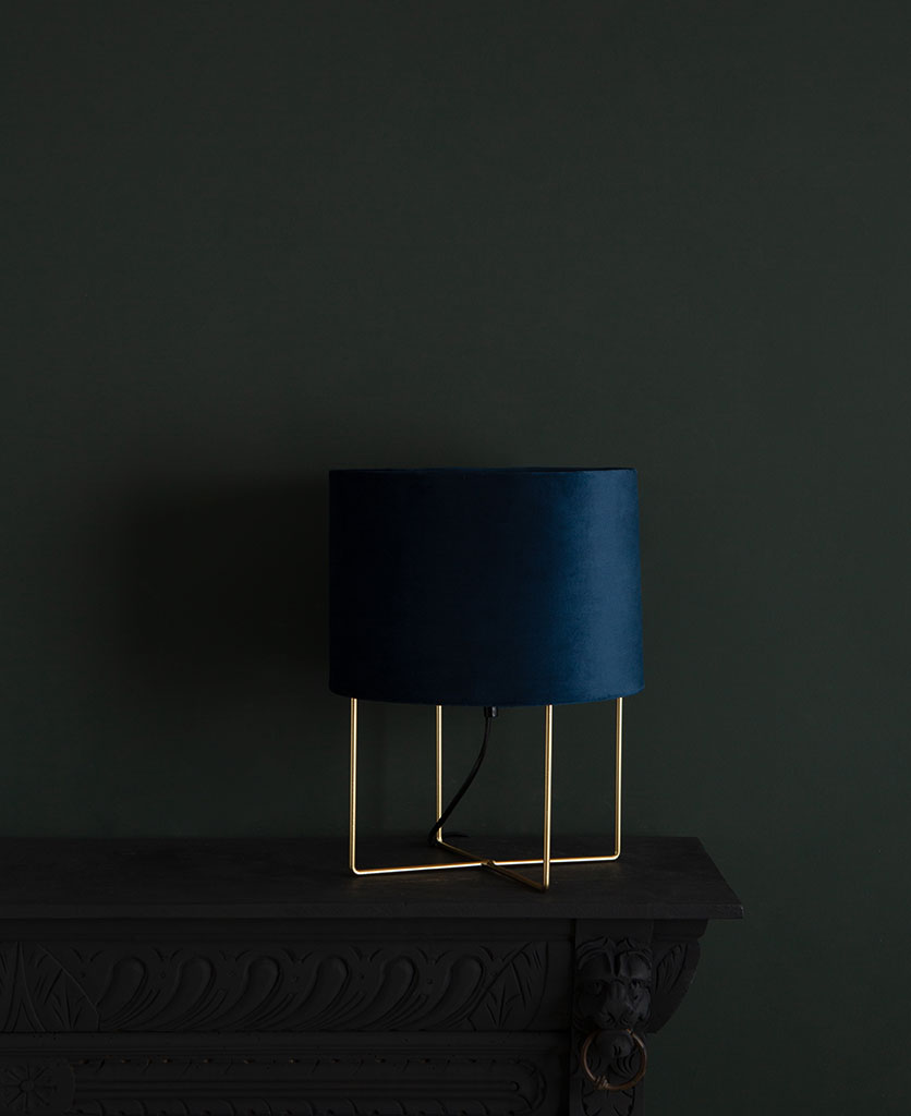 Harlow gold table lamp with blue velvet shade on dark background switched off