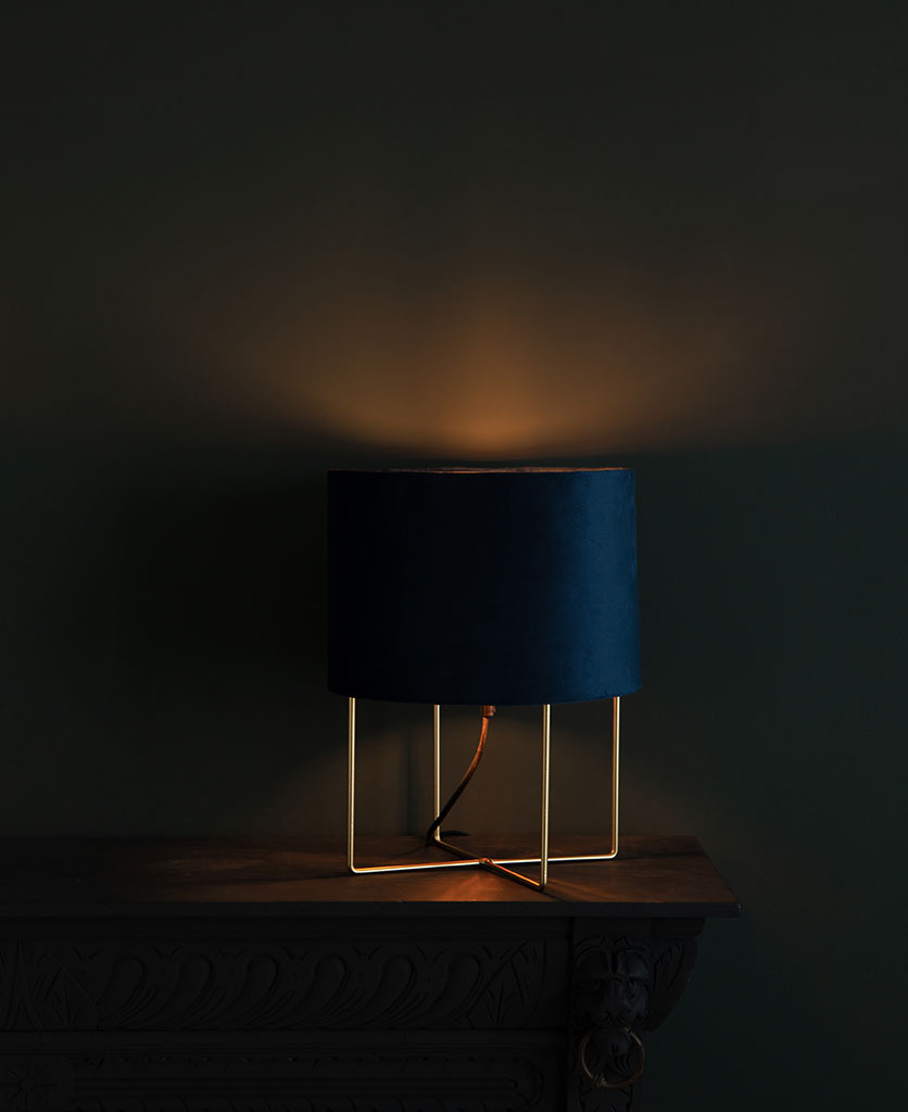 Harlow gold table lamp with blue velvet shade on dark background switched on