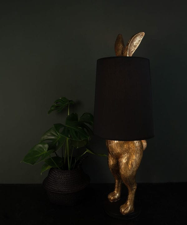 Hartley hare gold floor lamp with black shade on dark background switched on