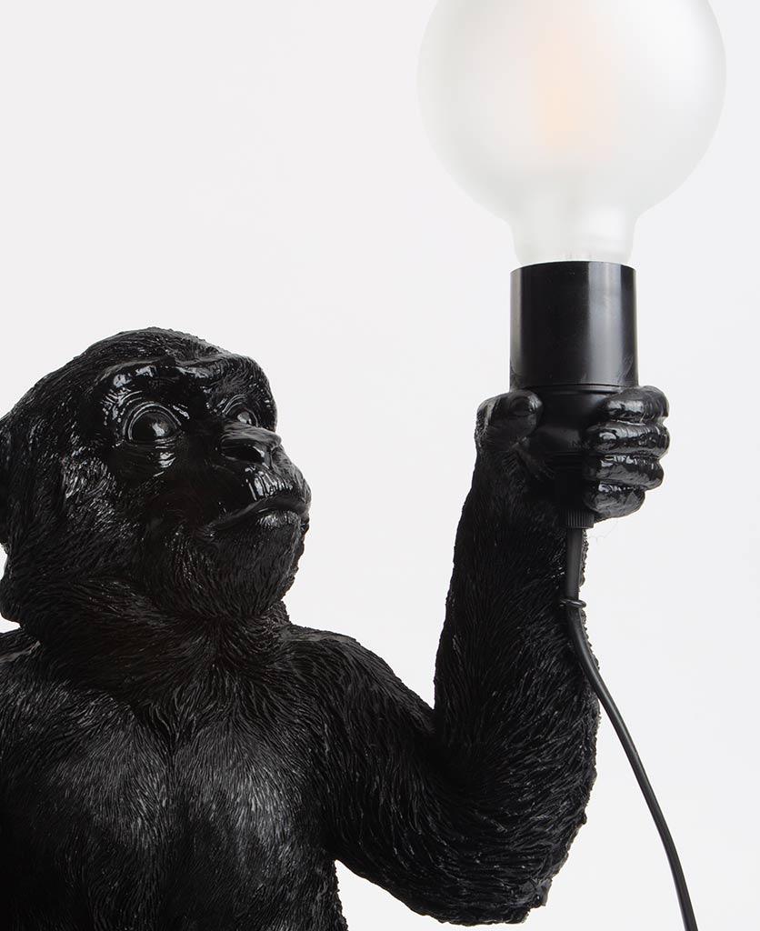 Close up of Abu black sitting monkey table lamp holding bulb on white background