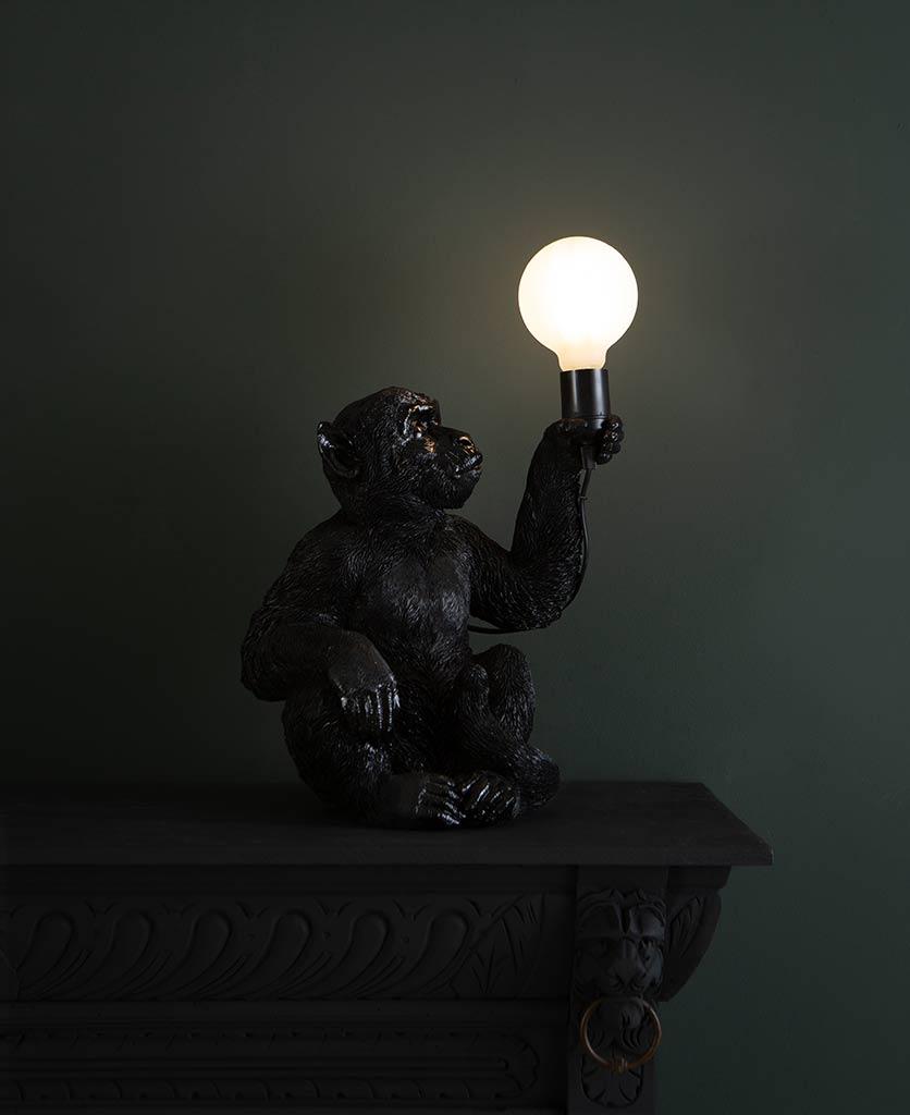 Abu black sitting monkey table lamp on dark background holding switched on lightbulb