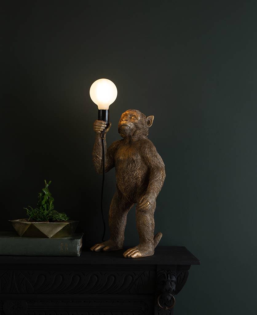 Koko gold standing monkey table lamp on dark background holding switched on lightbulb