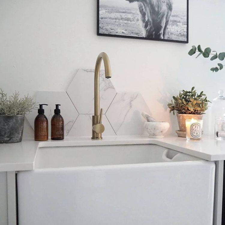 brass tinkasso tap above Belfast sink in a white kitchen