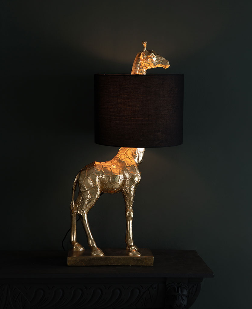 Sky gold giraffe table lamp with black shade on dark background switched on
