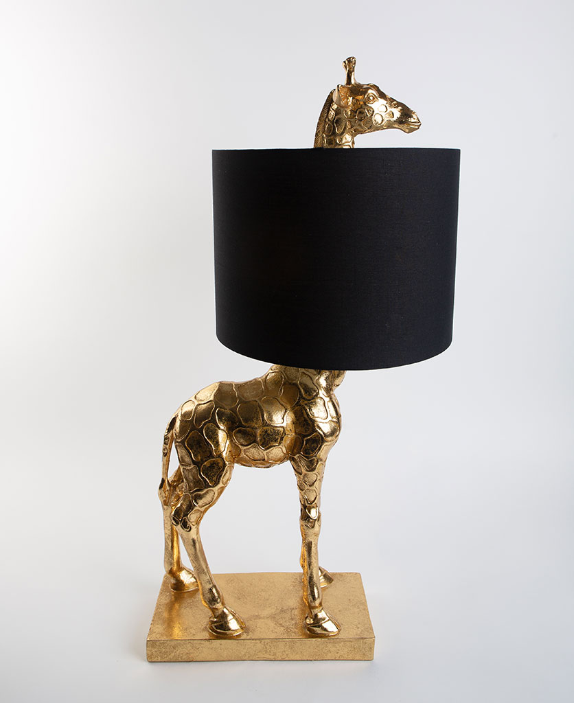 Sky gold giraffe table lamp with black shade on dark background on white background