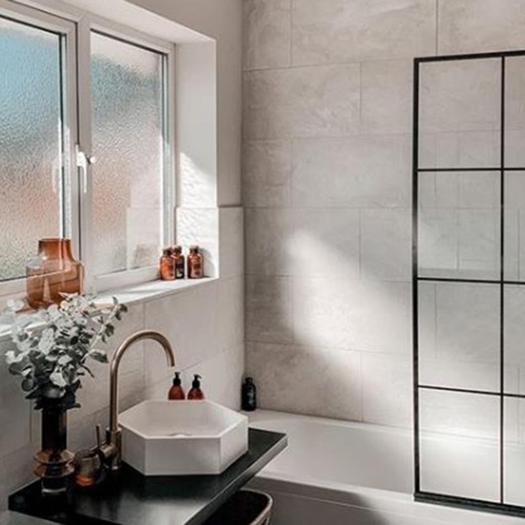 gold tinkisso tap next to white hexagonal sink in black and white bathroom