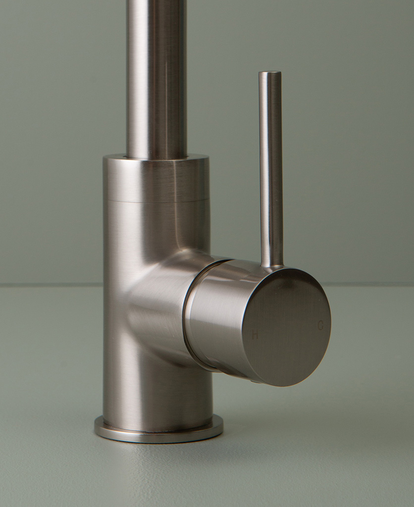 close up of silver tinkisso tap handle on grey-green background