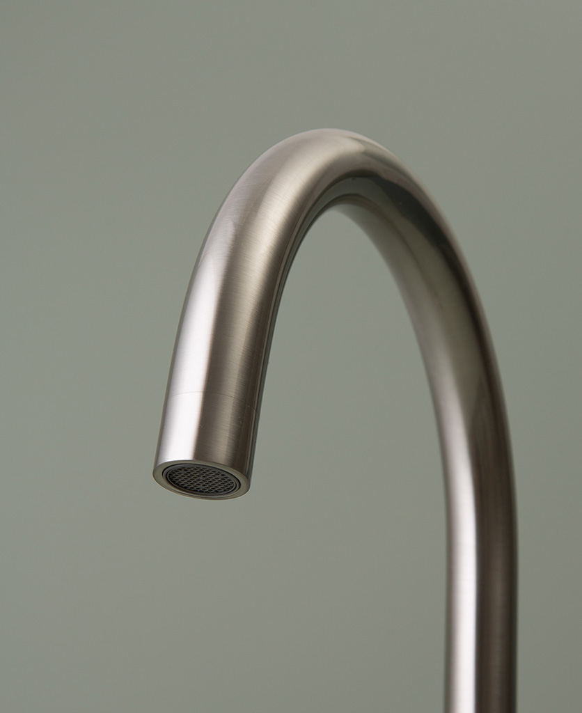 silver tinkisso tap spout close up on grey-green background