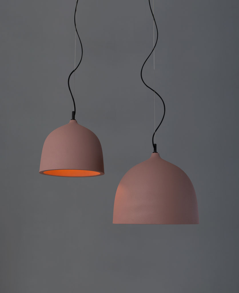 Boccia pink pendant light large and small suspended from black fabric cable against a grey background