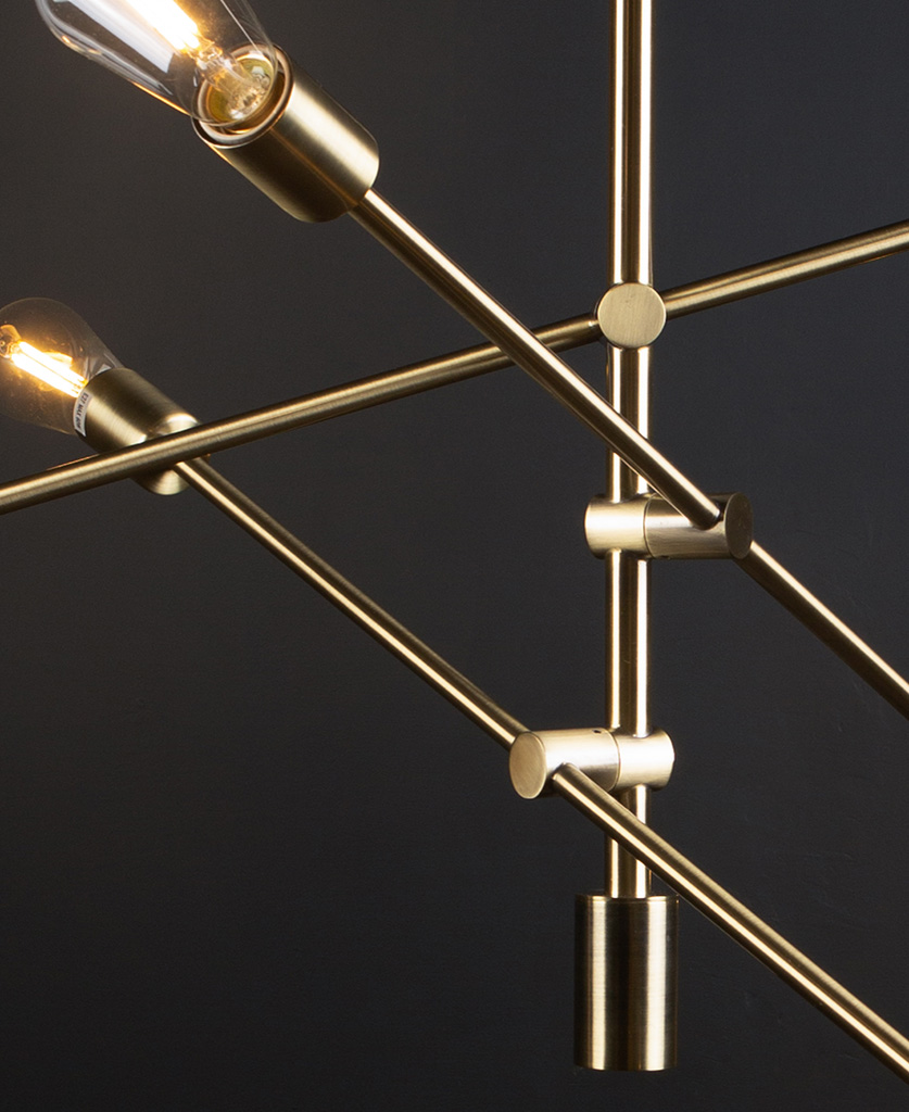brass feature pendant lights with clear pear bulbs close up against black background