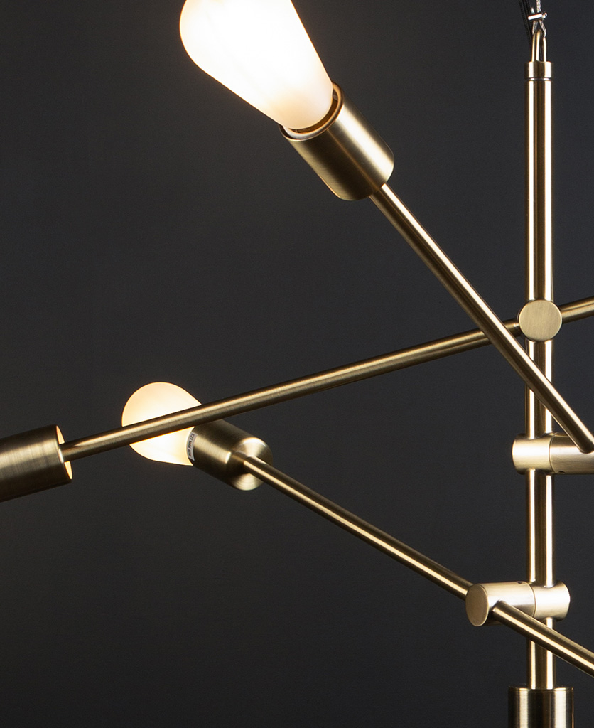 brass feature pendant lights with frosted pear bulbs close up against black background