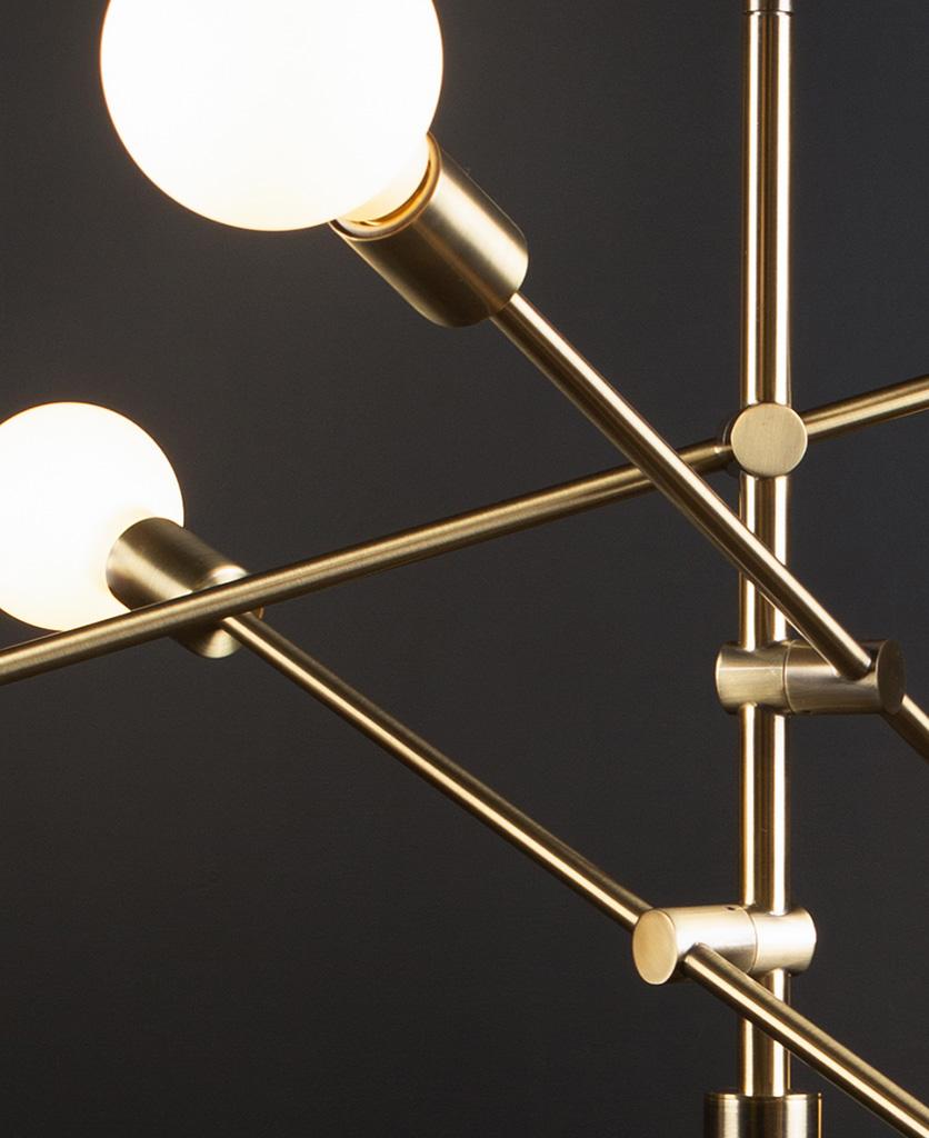 closeup of gold trikonsana pendant light with opal globe bulbs against black background