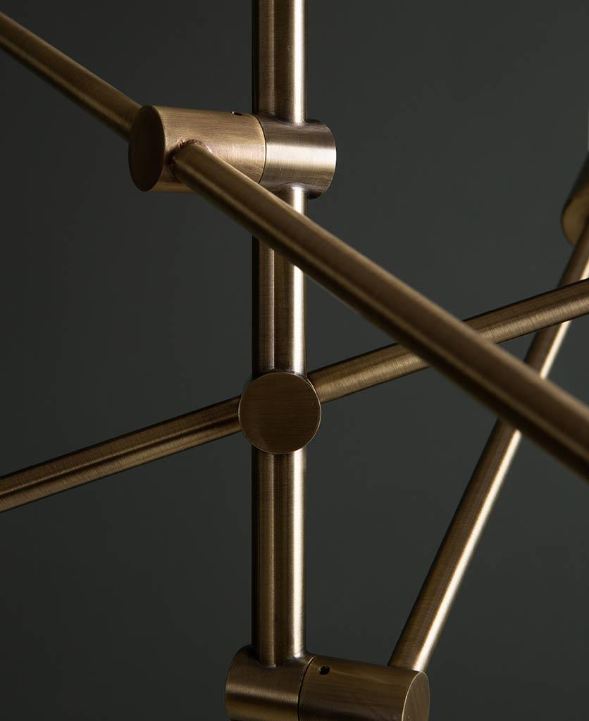 closeup of trikonasana gold pivoting arms on a black background