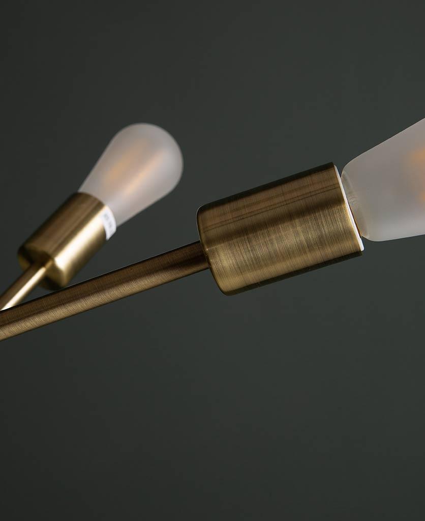 closeup of trikonasana gold frosted light bulbs against black background