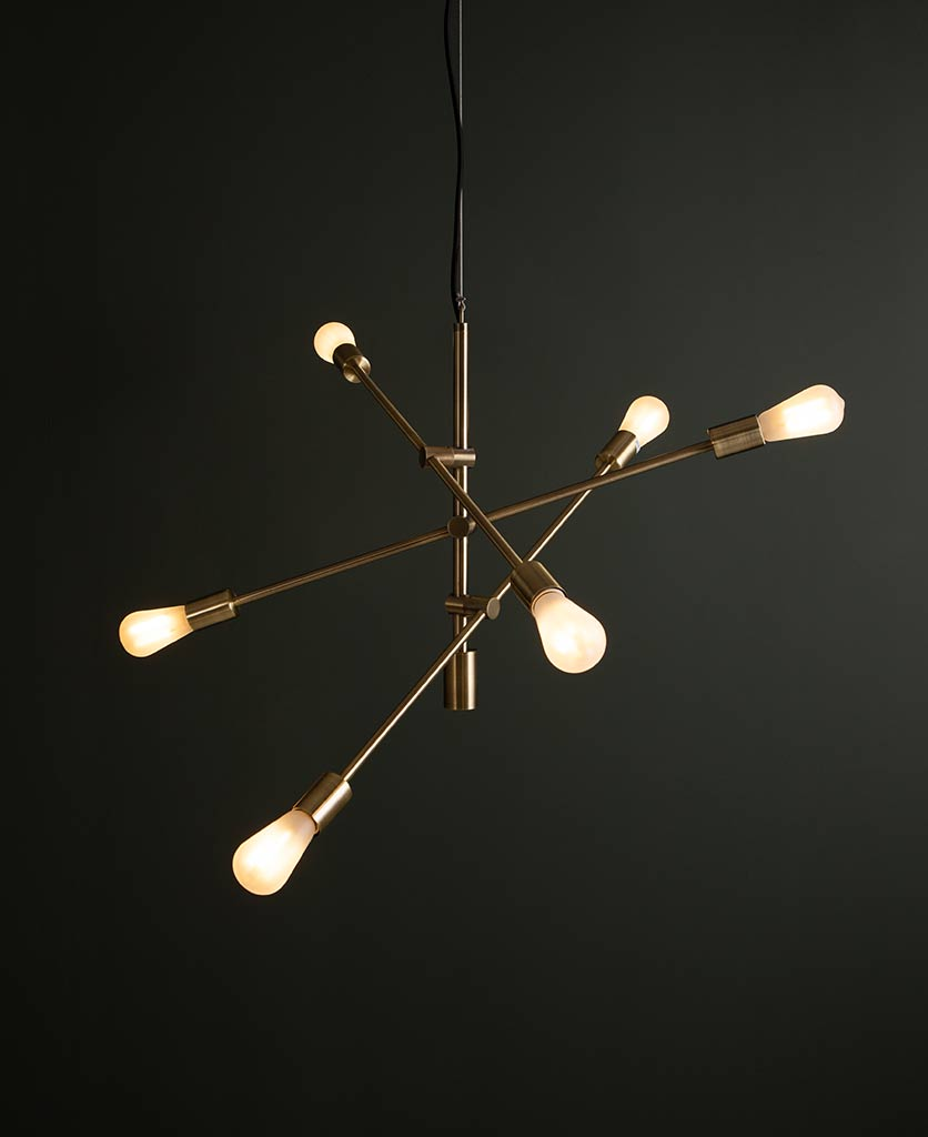 trikonasana feature pendant lights with three pivoting arms and six lit frosted light bulbs on a black background