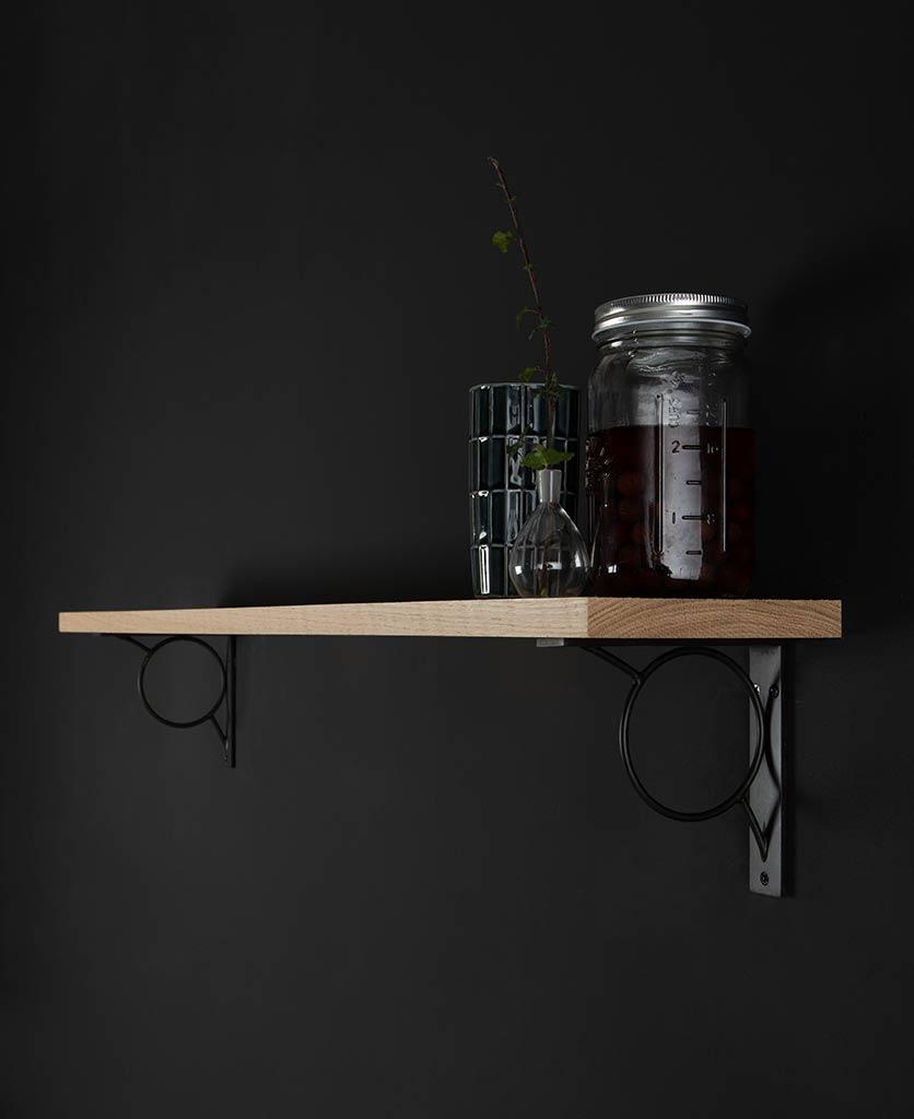 small mae oak shelf and brackets on black background