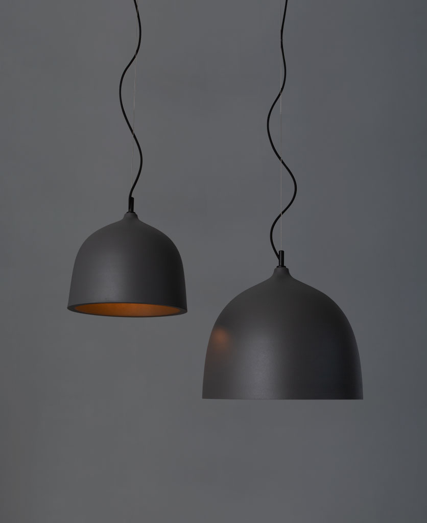 Trugo grey pendant light large and small suspended from black fabric cable against a grey background