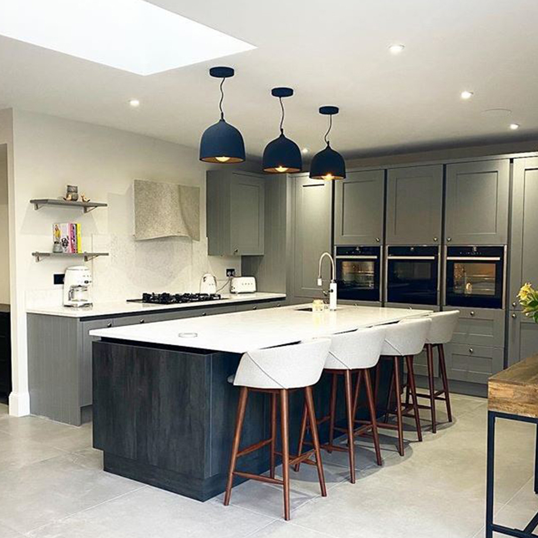three black round basque pendant lights suspended above a kitchen island in a grey and white kitchen