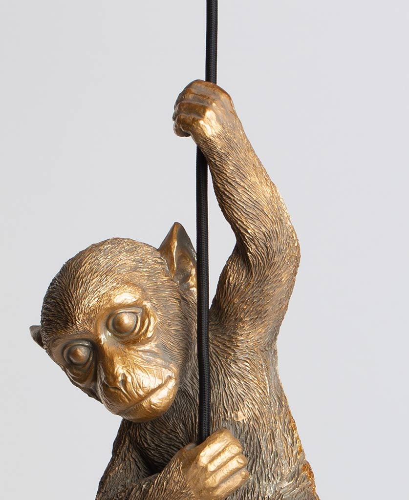 gold monkey pendant light suspended from black fabric cable on white background