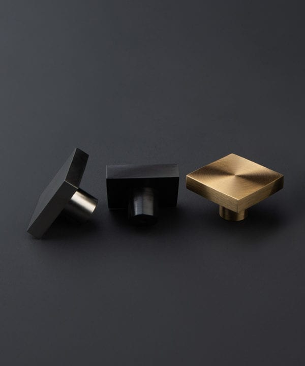 expressionist decorative drawer knobs in black silver and gold against dark grey background