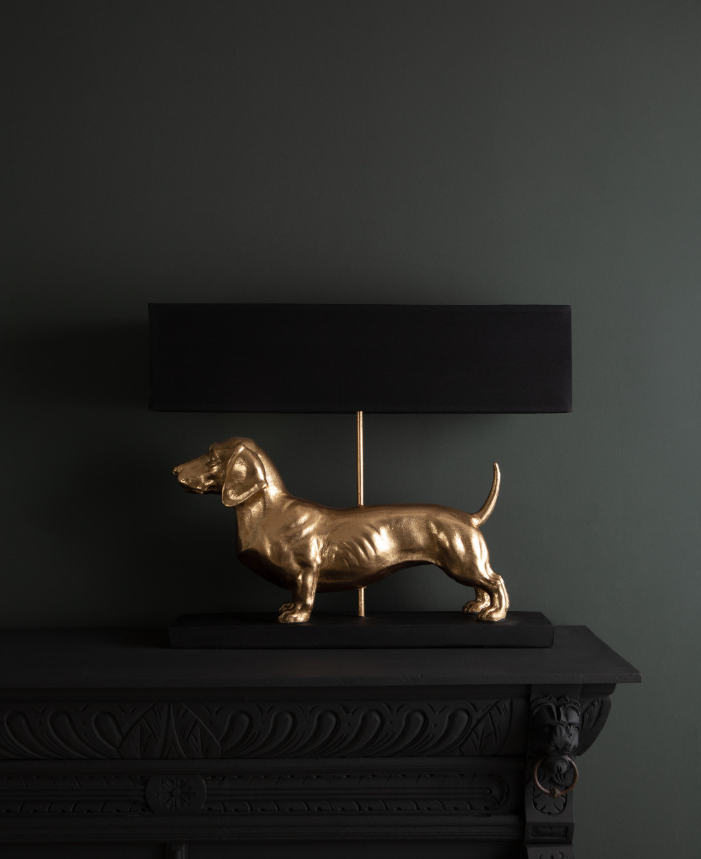 Fred dachshund gold dog table lamp with black shade on dark background switched off