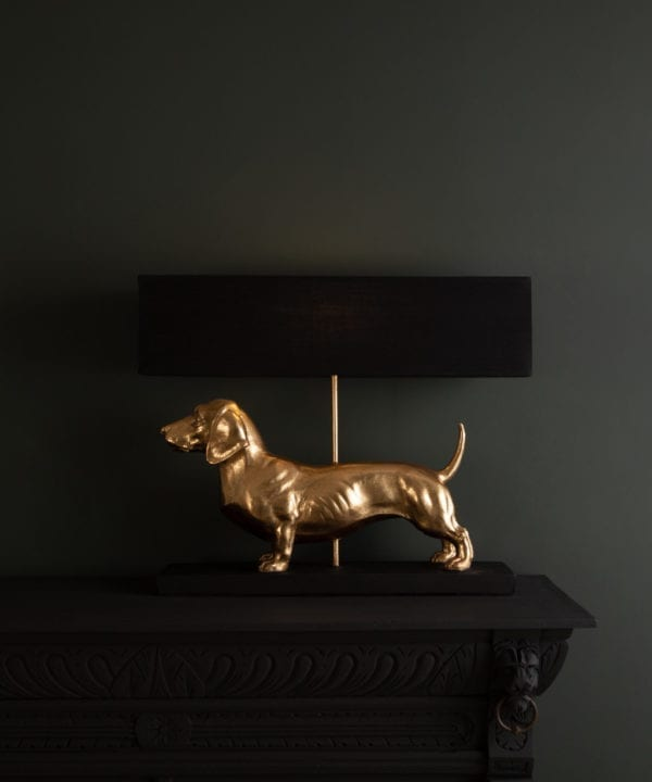 Fred dachshund gold dog table lamp with black shade on dark background switched on