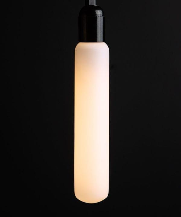 luna lit tube light bulbs with black bakelite bulb holder against black wall