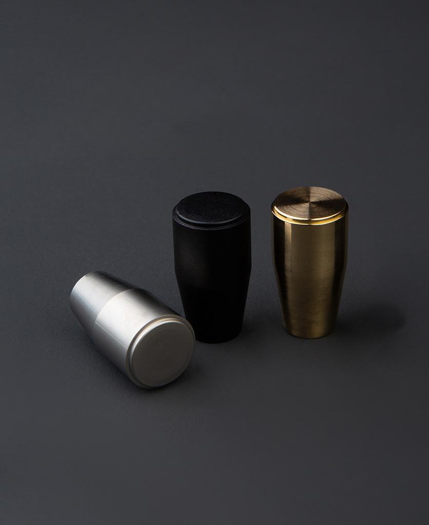 minimalist gold black and silver drawer handles against dark grey background