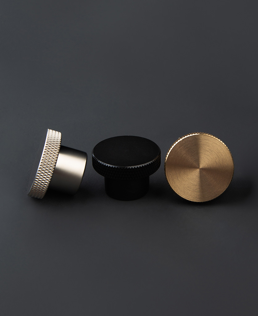modernist black silver and gold chest of drawer handles against dark grey background
