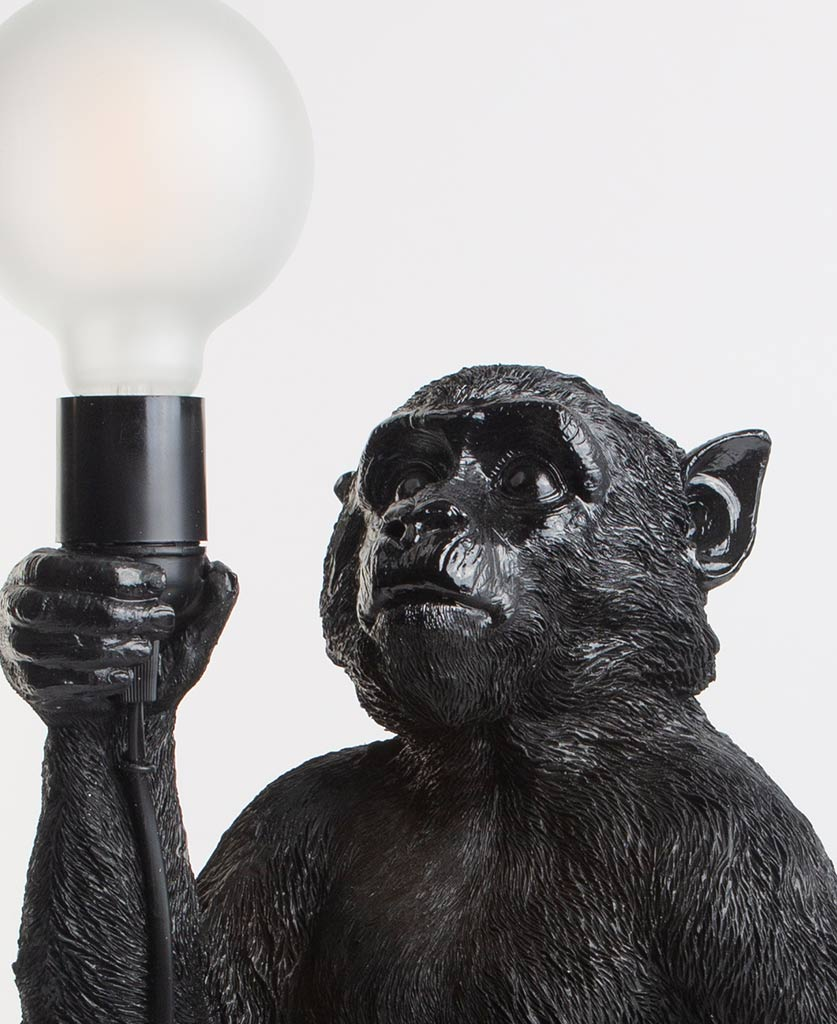Close up of Monty black standing monkey lamp holding switched off light bulb on white background