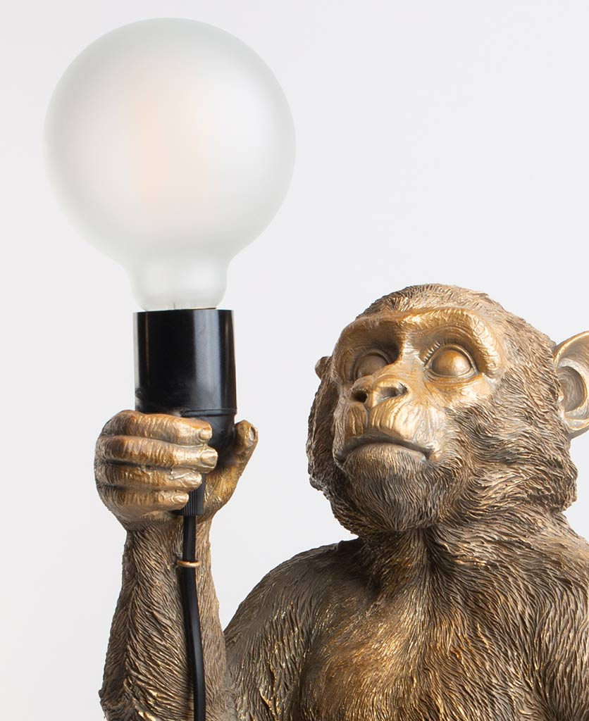 Close up of Monty gold standing monkey lamp holding switched off light bulb on white background