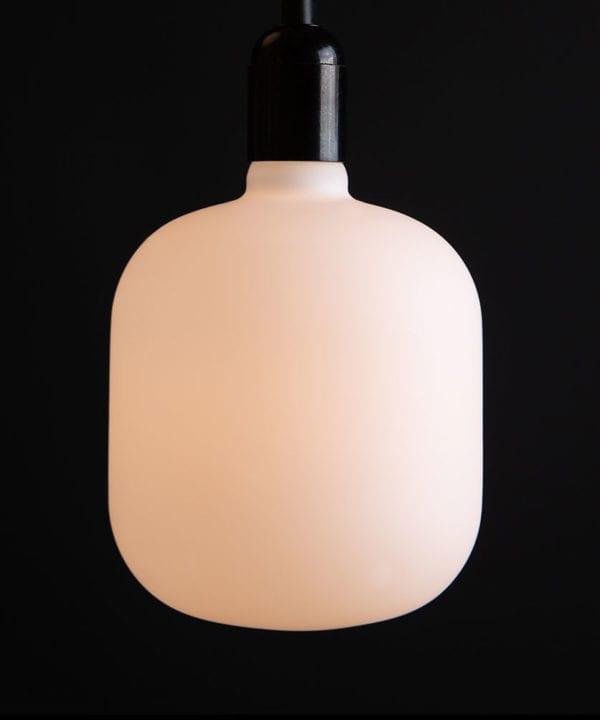 pandora lit square light bulbs suspended from black bakelite bulbholder against black background