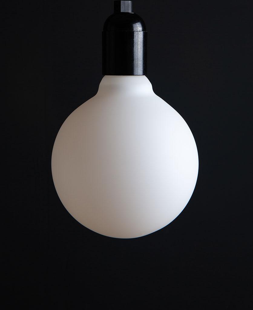 Unlit Aurora decorative light bulbs suspended from bakelite bulb holder against black wall